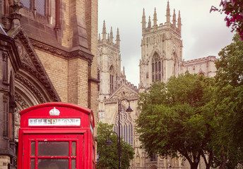 Old british red phone booth with the York Cathedral on the background