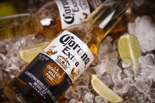 Two corona extra lager beer bottles  on ice with lime slices on a rustic wooden table - Cerveceria Modelo in Mexico