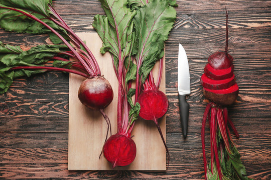 Fresh beets with cutting board and knife on wooden background