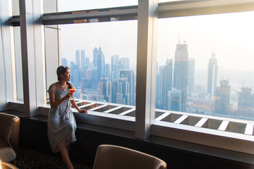 Woman enjoying a drink with downtown Dubai view