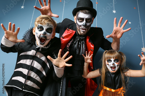 Father with children in Halloween costumes on color background