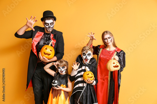 Family in Halloween costumes and with pumpkins on color background