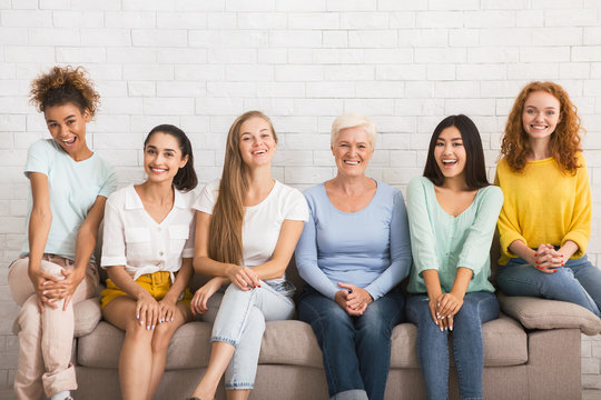 Smiling Diverse Women Sitting On Sofa Over White Brick Wall