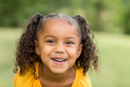 Cute mixed race little girl laughing and smiling.