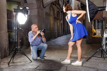 Photographer shooting female model on city street