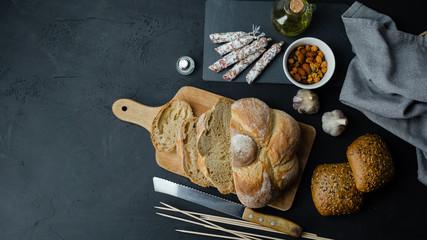 Pyszny chrupiący chleb z salami, orzechami, czosnkiem i oliwą. Widok z góry.