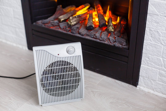 Heating radiator and a fireplace nearby in a white room with laminated wooden floor