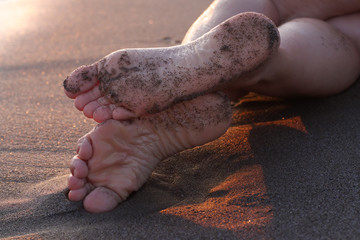 Female feet on the sand at sunset, with natural nail