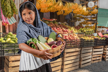 Girl selling variety of natural foods in the market. Little Latin girl with her basket full of local vegetables and fruit