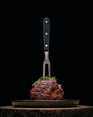 Sous-vide grilled beef steak with fork and herbs on dark background.