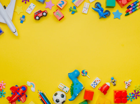 Frame of kids toys on yellow background with copyspace
