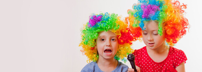 Funny image of cute child girls superstars singing with the microphone. Free space for text.