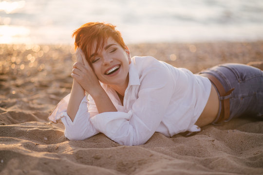 Woman with short hair on beach at sunset
