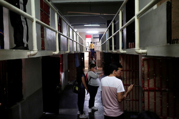 People take pictures of the empty cells of the Topo Chico prison during a closing ceremony in Monterrey