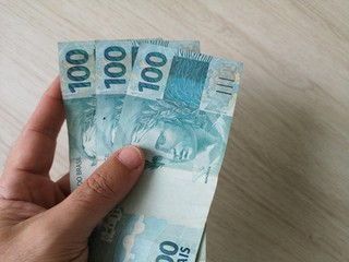 Brazilian Money - Hand holding one hundred reais banknotes