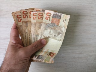 Brazilian money - Hand holding fifty reais notes