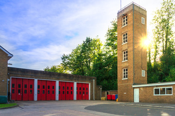 Facade of old fire station with red gates and tower close up against the background of the summer sky