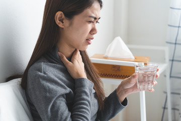 Sore throat in flu season. Young asian woman touching her neck and feeling pain in throat in the bedroom at home.