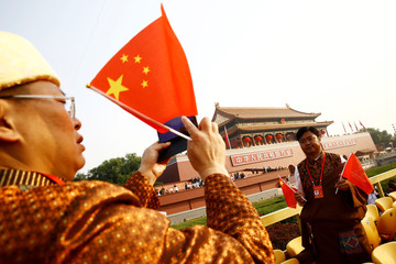 Delegate holding Chinese flags poses for pictures with Tiananmen Gate in the background before a military parade marking the 70th founding anniversary of People's Republic of China
