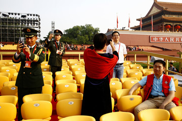 Delegates take pictures with mobile phones before a military parade marking the 70th founding anniversary of People's Republic of China