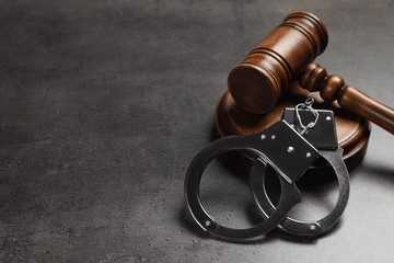 Judge's gavel and handcuffs on grey background, space for text. Criminal law concept