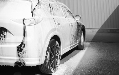 Luxury automobile covered with foam at car wash