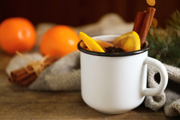 Mug with aromatic mulled wine on wooden table