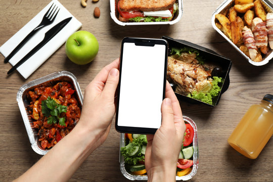Top view of woman holding smartphone over wooden table with lunchboxes,  mockup for design. Healthy food delivery