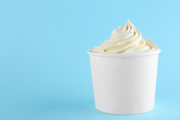 Cup with tasty frozen yogurt on blue background. Space for text