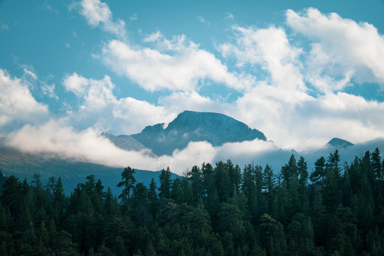 Shot of mountain peak poking through white puffy clouds on a sunny fall afternoon, RMNP Colorado