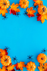 Nice halloween frame. Small spiders among leaves and pumpkins on blue background top view copy space