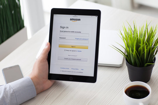Man holding iPad Pro with online shopping service Amazon