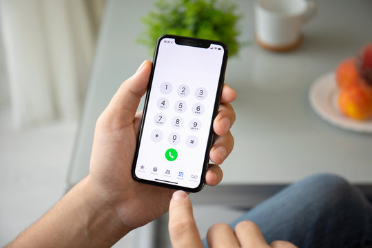 Man hand holding iPhone X with call number on screen