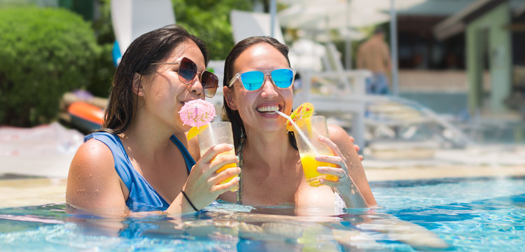 Two women drinking cocktails in a pool, on a summer vacation.