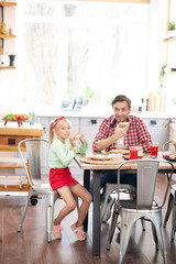 Daughter sitting near daddy and having breakfast together