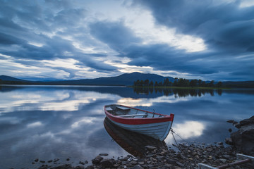 Fotomurales - Old rowboat at the rocky shore of a lake on a cloudy evening. Jamtland, Sweden.
