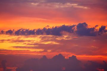 Hermoso cielo con nubes al amanecer con colores vivos, rojos y anaranjados.