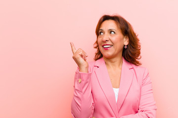middle age woman smiling happily and looking sideways, wondering, thinking or having an idea against pink wall