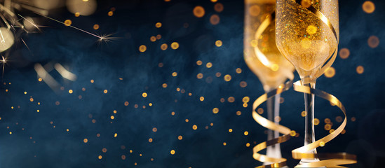 Poster Alcohol Two glasses of champagne with golden confetti, glitter, serpentine and lights.