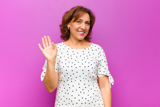 middle age woman smiling happily and cheerfully, waving hand, welcoming and greeting you, or saying goodbye against purple wall