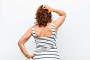 middle age pretty woman feeling clueless and confused, thinking a solution, with hand on hip and other on head, rear view against white wall