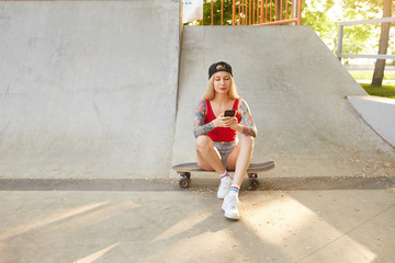 Outdoor photo of beauiful tattooed young blonde woman in baseball cap and casual clothes, sitting over city park on sunny day and looking at screen of her smartphone