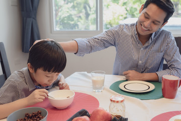 Asian family, father and son having breakfast together with mother in dining room, happy family concept