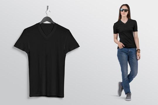 Hanging plain black v neck t shirt on wall. Beside standing beautiful female model in blue denim jeans pant.