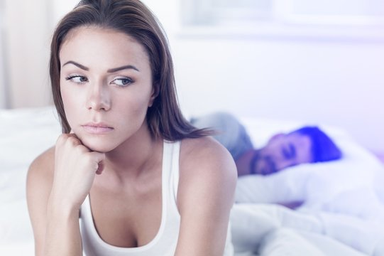 Dissatisfied beautiful young woman in bed with sad expression on her face, sex problems in long relationship or marriage while man sleeping. Saturation or satiety between caucasian couple, disinterest