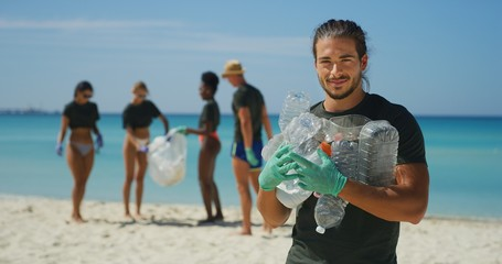 Portrait of an young male volunteer is smiling in camera satisfied with picking up a plastic litter...