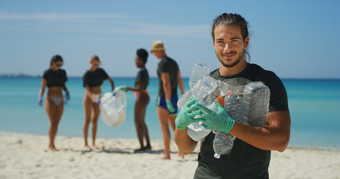 Portrait of an young male volunteer is smiling in camera satisfied with picking up a plastic litter on a beach with a sea to protect an environment.