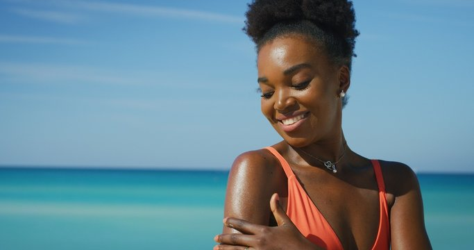 A happy young african woman is applying a sunscreen or sun tanning lotion to take care of her skin during a vacation on a beach.