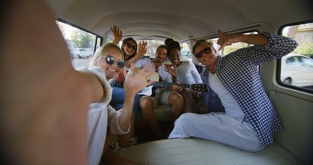 A group of young multi-ethnic friends are having fun to make a selfie or video call with a smartphone in minivan during trip on coastal road along the sea.