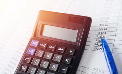Calculator with pen on white paper with numbers. Business and Finance accounting concept.
